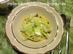 Tostada with beans, ricotta, lettuce, and cream